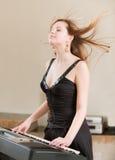 Girl plays keyboard synthesizer Stock Image
