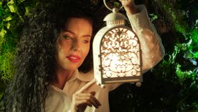 Girl plays with a lantern. A young curly woman holds in her hand a lantern inside which a candle is burning against the background of green leaves stock video