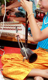 A girl plays a local Thai music instrument. Stock Image