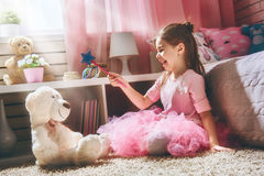 Girl plays with magic wand royalty free stock photo