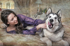 Girl plays with malamute Royalty Free Stock Images