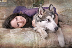 Girl plays with malamute Stock Images