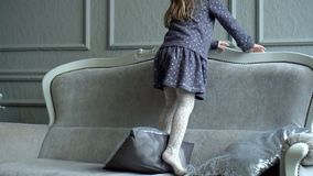 The little fair-haired girl plays with tails on a sofa at a Christmas tree. The lovely girl plays near the decorated. The girl plays near a New Year tree with a stock video