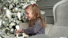 The little smiling fair-haired girl plays on a sofa at a fir-tree. The little girl looks in phone. Slow mothion. The girl plays near a New Year tree with a white stock video footage