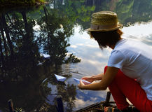Girl plays a paper boat on the river Stock Image