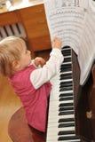 Girl plays  piano Stock Photos