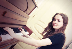 Girl plays piano. Cute and sexy adult girl is going to play piano Royalty Free Stock Photos