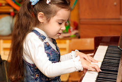 Girl plays piano Royalty Free Stock Photos