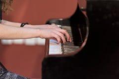 Girl plays piano Stock Image