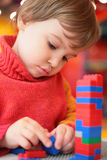 Girl plays with plastic constructor Stock Photos