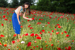 Girl plays in poppy field stock image