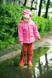 Girl plays in puddle Royalty Free Stock Image