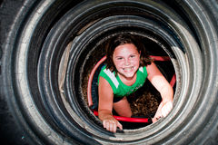 Girl plays in recycled tire tunnel Royalty Free Stock Photo
