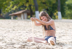 Girl plays with sand on the beach Royalty Free Stock Photos