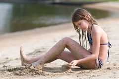 Girl plays with sand on the beach Stock Photo