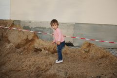 Girl plays with sand on construction Stock Images