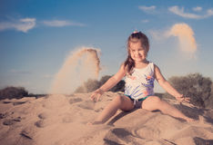 Girl plays by sand Royalty Free Stock Photo