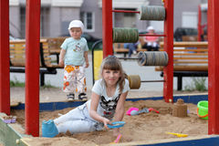 Girl plays in sandbox Stock Photography
