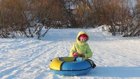 Girl plays with snowtube and hides behind it at hill at sunny winter day stock footage