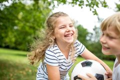 Girl plays soccer with brother royalty free stock photography