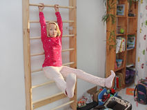 Girl plays sports on Wall bars in the children`s room Royalty Free Stock Photo