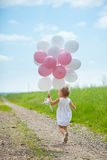 Girl plays in summer park with colorful baloons Stock Photos
