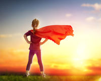 Girl plays superhero. Little child girl plays superhero. Child on the background of sunset sky. Girl power concept