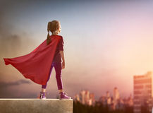 Girl plays superhero. Little child girl plays superhero. Child on the background of sunset sky. Girl power concept Stock Images