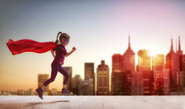 Girl plays superhero. Little child girl plays superhero. Child on the background of sunset sky. Girl power concept Stock Photography