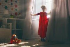 Girl plays superhero royalty free stock photo