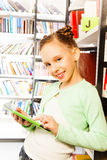Girl plays with tablet near bookshelf in library Royalty Free Stock Photo