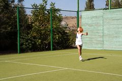 Girl plays tennis. Lucky girl and a friend played tennis on the court Royalty Free Stock Photo