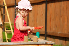 The girl plays to a sandbox.Horizontal format. Stock Images