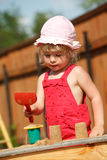 The girl plays to a sandbox.Vertical format. Royalty Free Stock Image