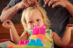 girl plays toy constructor father brushes her hair closeup Stock Image