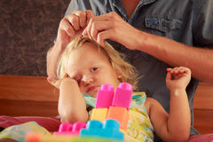 girl plays toy constructor father brushes her hair closeup Royalty Free Stock Image