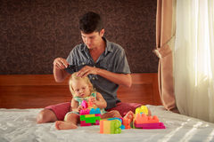 girl plays toy constructor father brushes her hair Royalty Free Stock Images