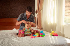 girl plays toy constructor father brushes her hair Royalty Free Stock Photo