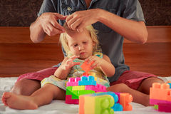 girl plays toy constructor father brushes her hair Royalty Free Stock Image
