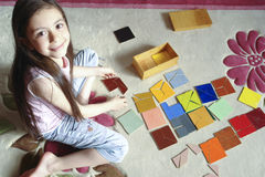 Girl plays traditional tangram game. 8 years old girld plays tangram game stock image
