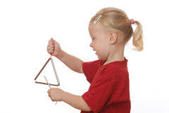 Girl plays triangle Royalty Free Stock Photo