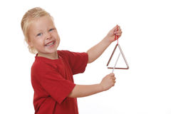 Girl plays triangle. Portrait of a young girl playing a triangle on white background royalty free stock image
