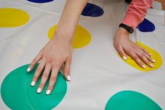 A Girl Plays Twist Game on the Floor, Hand on Colorful Circles. Trends in children& x27;s anti-stress toys for attention stock images