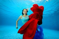 The girl plays underwater with a red cloth and looks at the camera. Portrait. Shooting under water. The landscape view Royalty Free Stock Photography