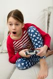 Girl Plays Videogame. A schoolgirl plays a videogame with a game controller, showing a lot of excitement Stock Image