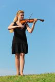 Girl plays violin against  sky Royalty Free Stock Images
