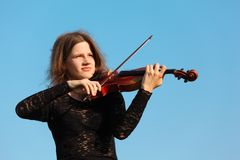 Girl plays violin against  sky Royalty Free Stock Photo