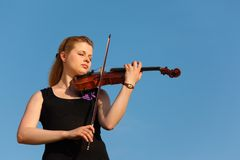 Girl plays violin against  sky Stock Images