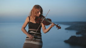 Girl plays violin staying near the beautiful stock footage