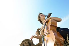 The girl plays a violoncello. The beautiful girl plays a violoncello in the field against a cathedral stock photography